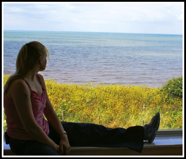 Sarah sat in the window of the lighthouse looking out over the sea