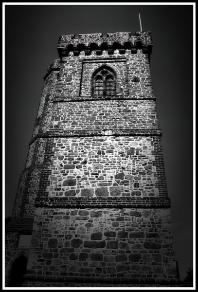 A framatic black and white photo looking upwards of the tower from the outside
