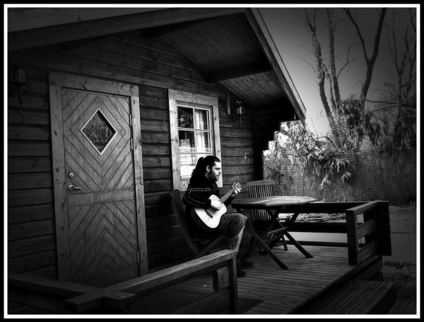 Me playing my baby Taylor on the porch on the log cabin