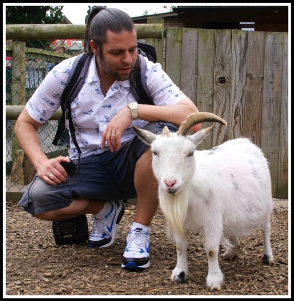 Me kneeling down next to a little goat