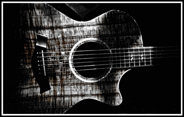 A black and white photo of my Taylor Koa K22 with lots of textured shadows