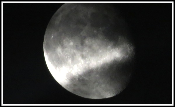 A centred photo of the moon slowly being covered with dark clouds