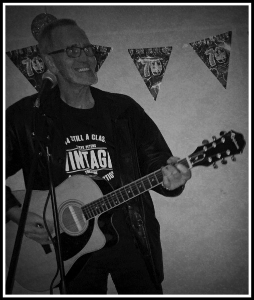 Sarah's dad playing guitar in front of 70th birthday banners