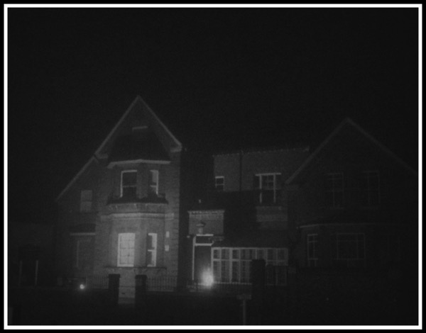 An old school building covered in fog illuminated in the darkness