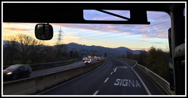 Photo while sat on the coach taken looking through the windscreen overlooking the mountains with Siena written on the road