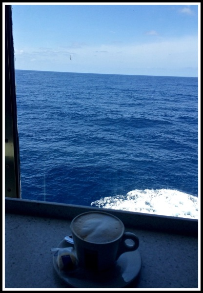 A Cappuccino on a window seat looking out over a beautiful blue seaat sea