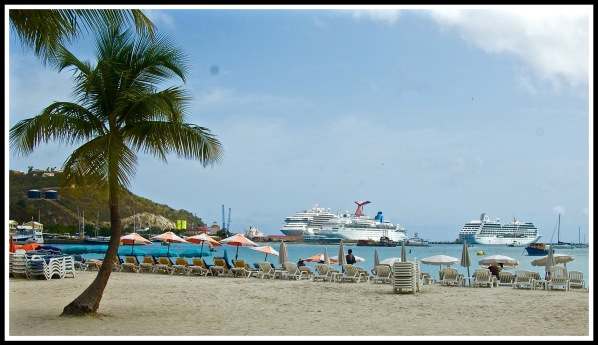 Photo of the beach, with a palm tree on the left, and 2 cruise ships on the right