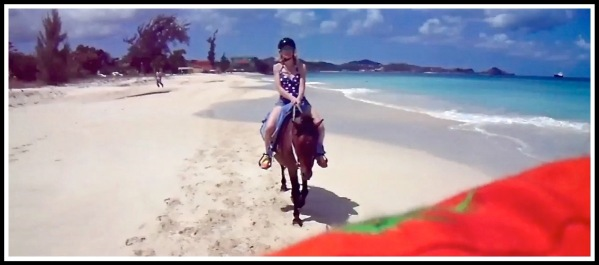 Photo of Sarah on her horse riding across stunning beach landscape with my orange shirt at the bottom as i took the photo over my shoulder