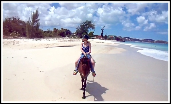 Sarah on her horse looking inland as she rides across the stunning beach