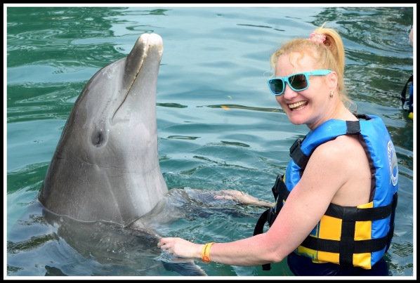 Sarah stood on the right holding both flippers whilst having a dance with the dolphin