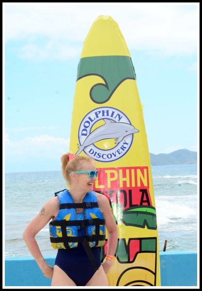 Sarah wearing swim suit and life jscket, stood in front of a large surf board promoting the dolphins