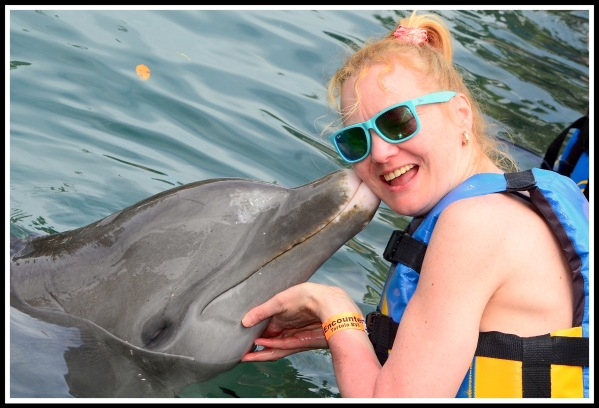 Sarah getting a kiss from the dolphin