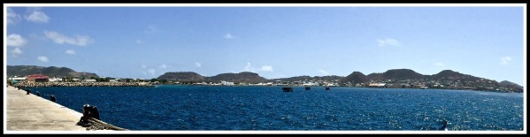 A panorama taken from the dock pier overlooking the amazing span of volcano hills with the vivid blu sea in front