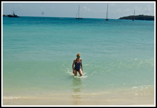 landscape shot of Sarah walking out of the turquoise sea, onto yellow sands, with sailing ships in the far distance