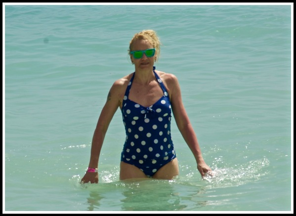 close up of Sarah walking out of the see,with the water up to her hips. Sarah is wearing her fave spotted puple swimsuit