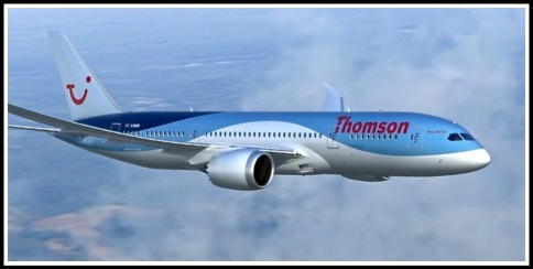 A photo of the Thomson 787 Dreamliner in flight above the clouds, flying from left to right