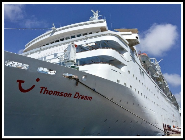 A colour photo of the Thomson Dream cruise ship standing from the dock and looking up