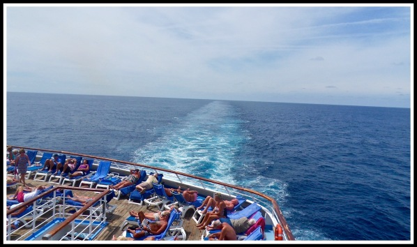 A view of the ocean from the rear of the ship, overlooking the sunbathing area at the bottom of the shot