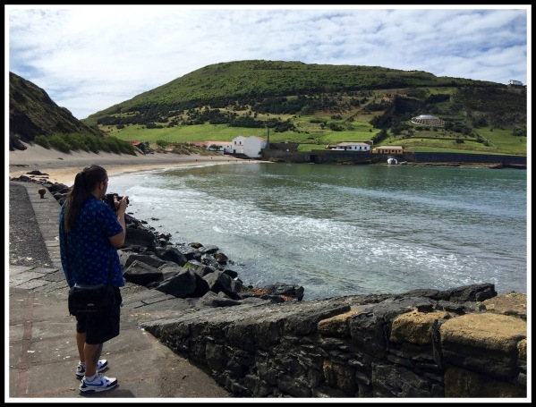 Me stood on the left with volcanic rock beach all around and a view of the bay