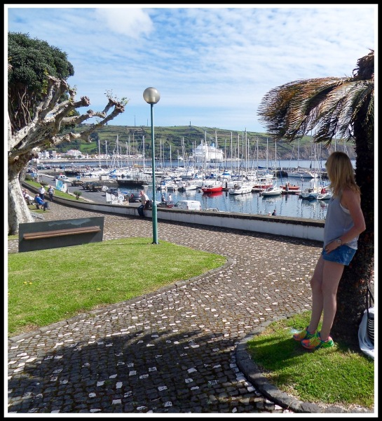Sarah leaning on a palm tree on the right with the Horta marina and bay filling the rest of the image