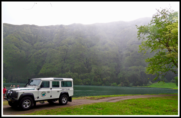 A 4x4 parked in front of a huge volcano and river