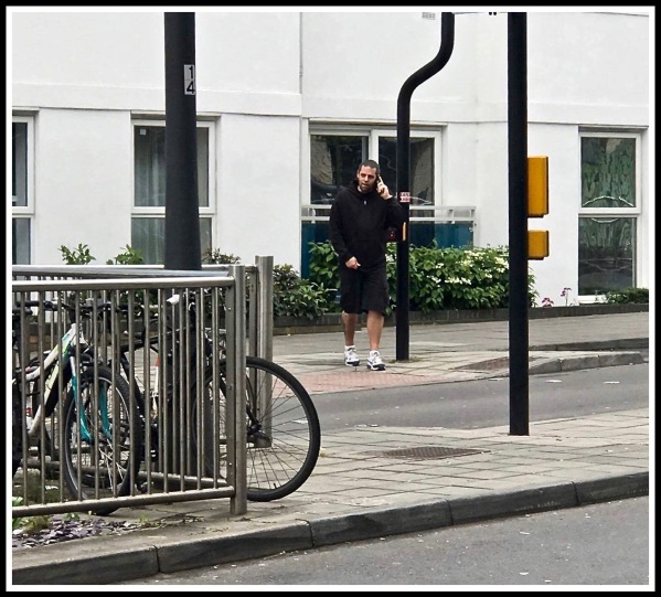 A photo of me crossing road to train station while talking on the phone wearing a black hoody, black shorts and black and white trainers