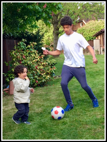 Vini playing football with his brother Raffy whilst holding an ice-cream