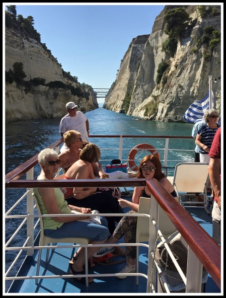 Photo of rear of boat showing people sat looking down Corinth canal.