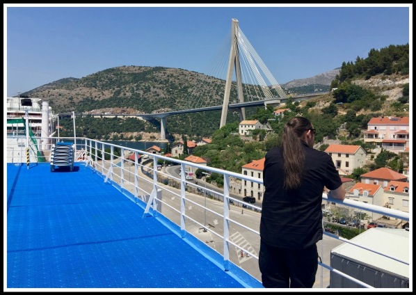 Me lent against the railing looking out across the landscape and bridge of Dubrovnik