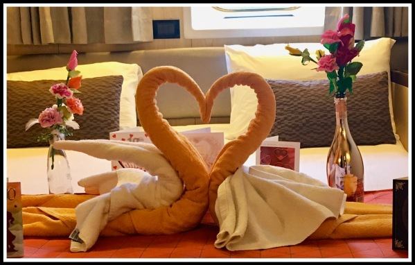 two towel swans together in a love heart shape surrounded by our anniversary cards, on the bed of our cabin on the ship