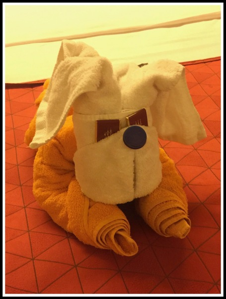 A towel folded into a puppy dog with chocolates as his eyes
