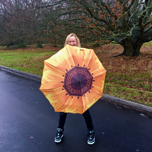 Sarah walking along a wet road with a bright yellow sunflower umbrella facing the camera, and her lovely smile is just above.