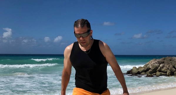 Me wearing a black best and orane shorts waling along the beach in Barbados with braided hair too