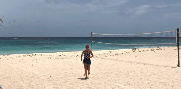 Sarah running towards the camera with a volley ball net on the right on the Barbados beach. The sea is behind her