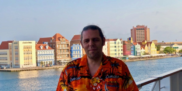 Me stood in front tof the colourful Curacao buildings wearing a Curacao orange shirt