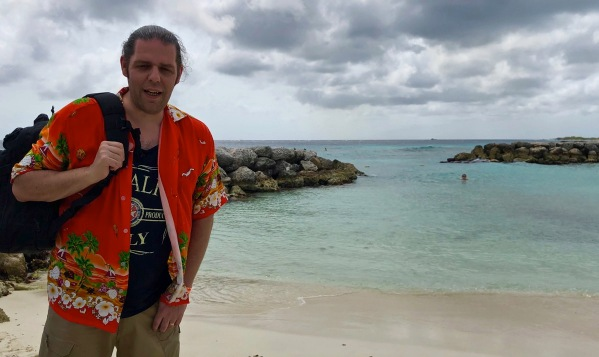 Me stood on the left in a orange caribbean shirt carrying a black backpack with views of palm island, Aruba in the background