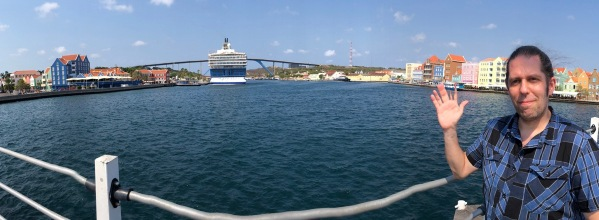 Me stood on the right of a panorama with the boat in the centre and the colourful buildings behind me.