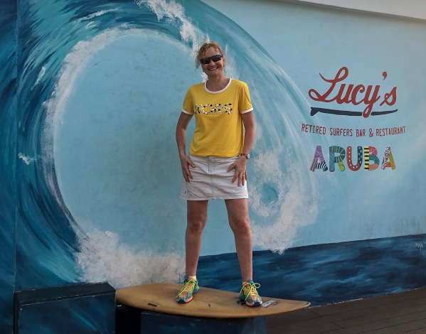 Sarah stood on a surf board in her new yellow Michael Kors t-shirt.