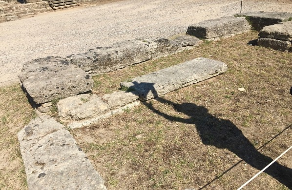 A shadow across the sandy floor of our guide pretending to light the torch from the ancient games at the exact spot