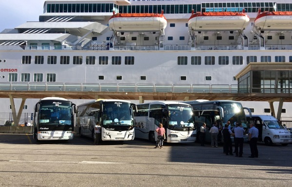 row of coaches in front of the ship