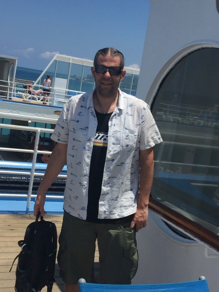 Full shot of me looking at the camera with shades on stood on the deck of the ship