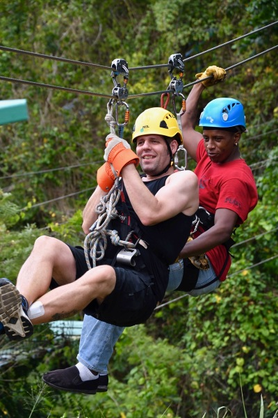 Me on the zip line with the zip line dude attached to me and we are high above the rain forest