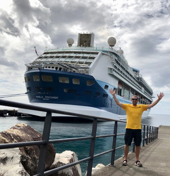 Me in a bright yellow t-shirt waving my arms in the air in front of the cruise ship