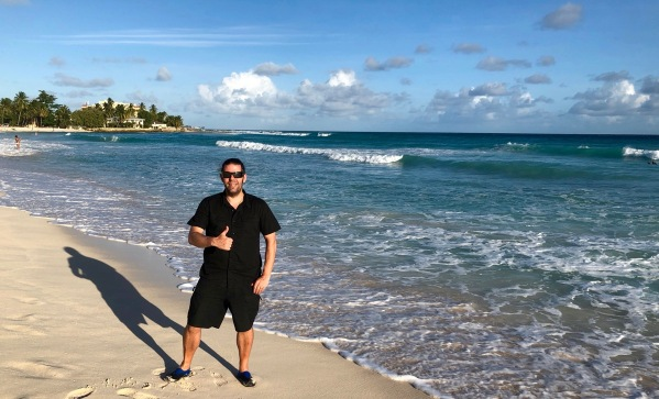 Me stood on the beach with my thumb up in Barbados
