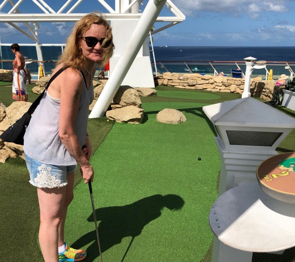 Sarah playing crazy golf on the top deck of the ship