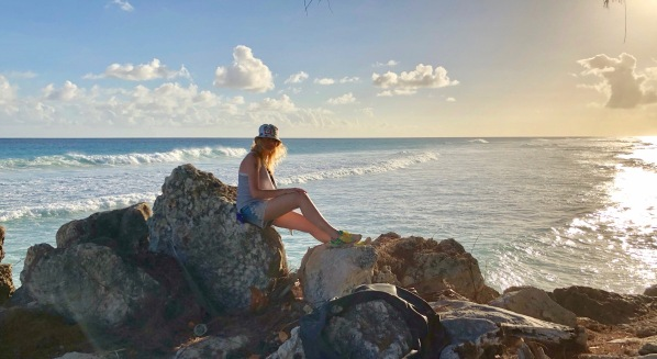 Sarah sat on the rocks in front of the beautiful Bajan sunset