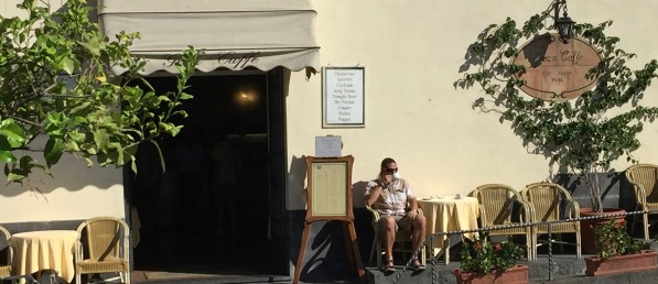 Me sat in the sun outside the cafe eating a coissant and drinking an espresso ith the road right in front of me