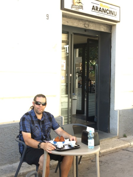 me sat outside the Arancinu place with the arancini on a plate with a coffee