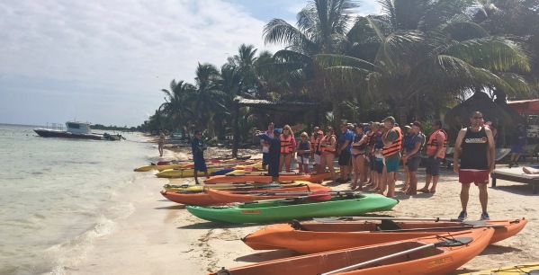 Me stood on the beach next to lots of kayaks with another group being shwed hwo to use them