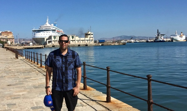 me stood on the dock carrying the blue sicily baseball cap i'd just bought with the seascape of boats behind me